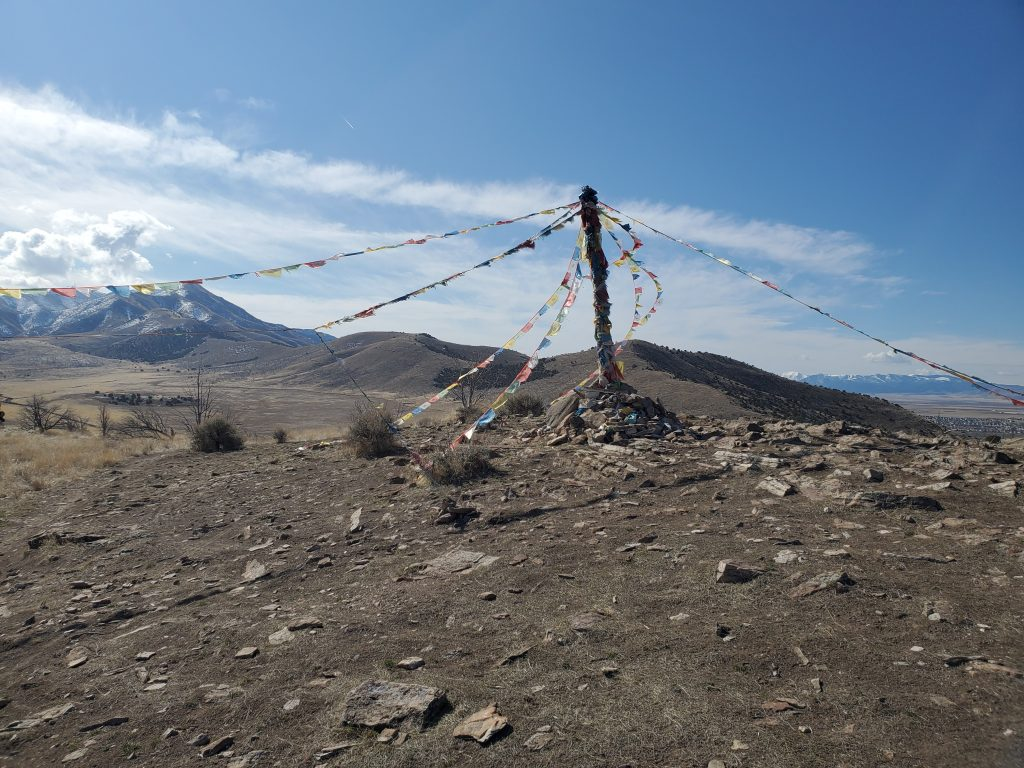 Rocky scene with prayer flags and mountains in the background