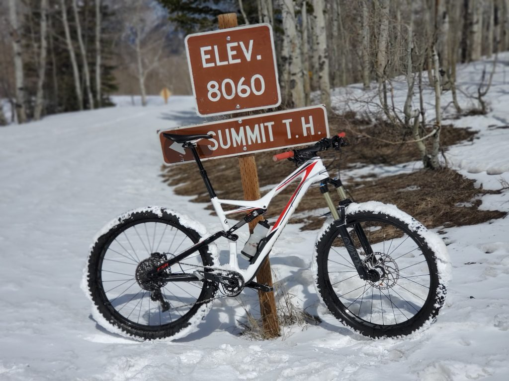 Mountain bike leaning on an elevation sign (8060ft) in the snow